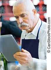 senior salesman using digital tablet in wine shop