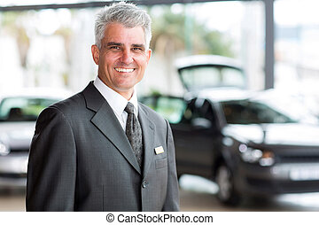 senior salesman working at a car dealer - senior vehicle...