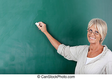 Senior school teacher writing on blackboard