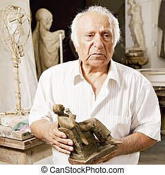Senior sculptor holding his sculpture and looking sideways