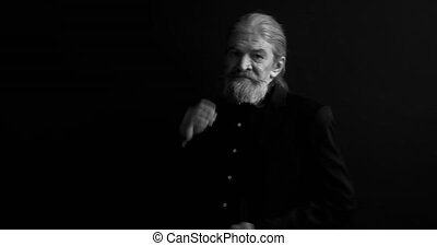 Senior serious man with whitened beard in dark business clothes standing sideways in semi-lit room on black background. Black and white portrait. Mature man on black background. Prores 422.