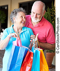 Senior Shoppers - Look What I Got - Senior man looks in the...