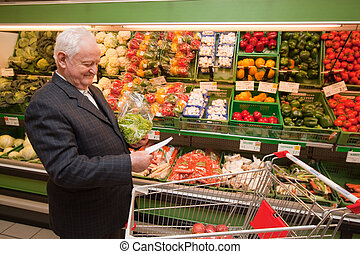 senior shopping for food in supermar - a senior shopping for...