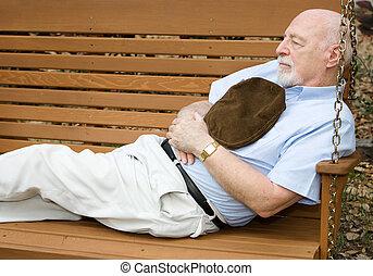 Senior man taking a nap on a park swing.
