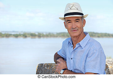 Senior sightseer looking over an estuary from an elevated...
