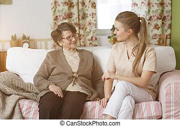 Senior sitting with her nurse