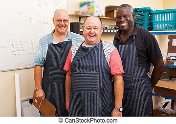 senior small business owner and employees - happy senior...