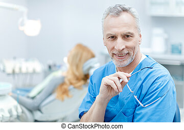 senior smiling dentist in uniform in dental clinic with patient behind