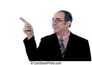Senior smiling director pointing away