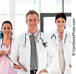 Senior Smiling doctor with his colleagues in front of the...