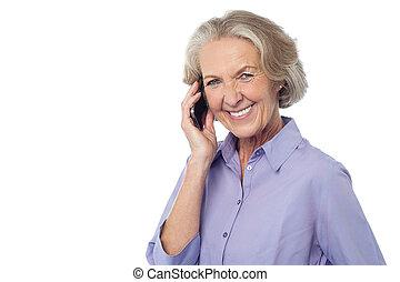 Senior smiling lady attending phone call