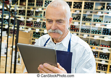 senior sommelier using digital tablet