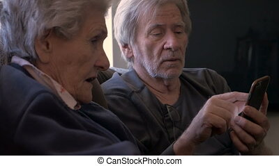 Senior son shows his older mother how to use a smart phone -...