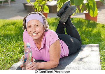 Senior sportive woman lying on mat sunny - Senior sportive...