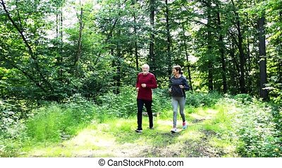 Senior sporty couple running in the forest outdoors in sunny nature.