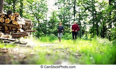 Senior sporty couple running in the forest outdoors in sunny...