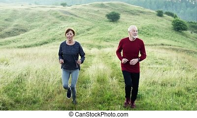 Senior sporty couple running on meadow outdoors in foggy nature.