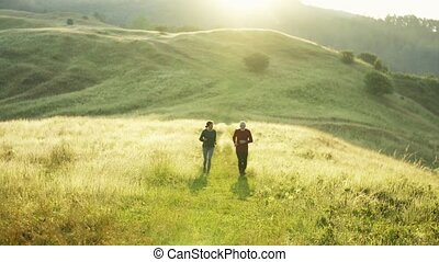 Senior sporty couple running on meadow outdoors in nature at...