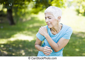 Senior sporty woman has shoulder pain in the park