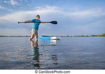 senior paddler is stretching and warming up before morning workout on a stand up paddleboard - Boyd Lake State Park in northern Colorado
