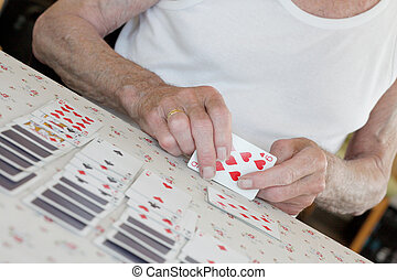 Senior playing solitaire