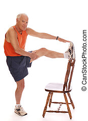 Senior Stretches - Senior man stretching leg muscles by...