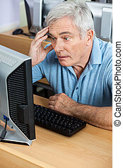Senior Student Looking At Monitor During Computer Class