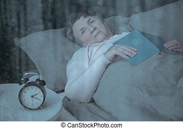 Senior suffering from insomnia lying in bed with book