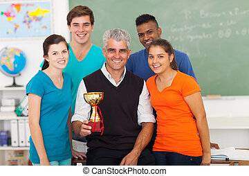 senior teacher and high school students with trophy