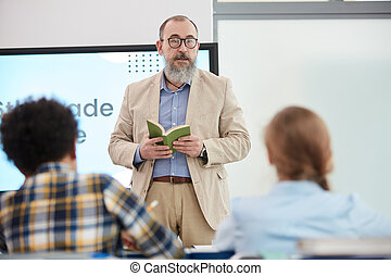 Senior Teacher Talking to Kids during Lesson