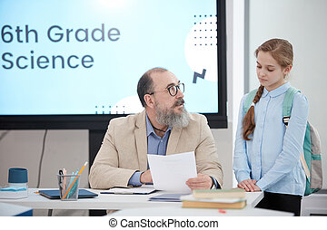 Senior Teacher Talking to Student in Class