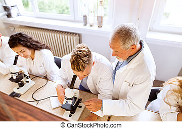 Senior teacher teaching biology to high school students in labor