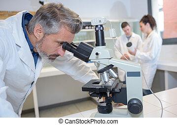 Senior technician looking into microscope