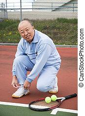 Senior tennis player - A shot of a senior asian tennis...