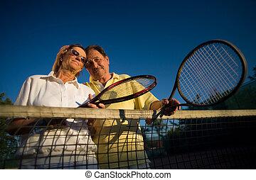 Senior tennis players - Active senior couple is posing on...