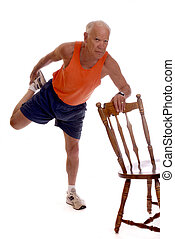 Senior Thigh Stretch - Senior man balancing on one let while...