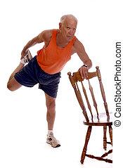 Senior Thigh Stretch - Senior man balancing on one let while...