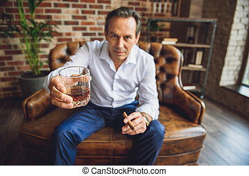 Senior tired businessman with glass of whiskey