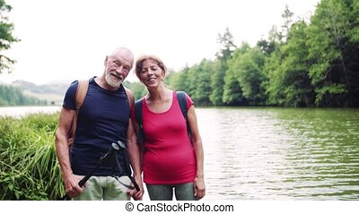 Senior tourist couple on a walk in nature, standing by lake.
