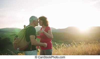Senior tourist couple travellers hiking in nature, kissing when resting. Slow motion.