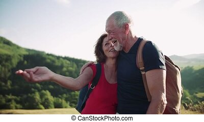 Senior tourist couple travellers with backpacks hiking in nature, talking.