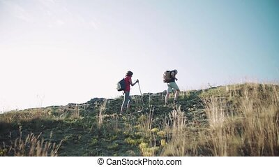 Senior tourist couple with backpacks hiking in nature.