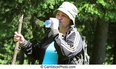 Senior tourist woman drinking water