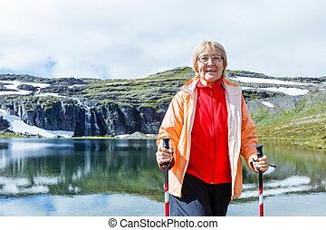 Senior tourist woman hiking.