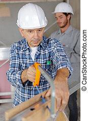 senior tradesman using hacksaw