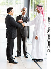 senior translator introducing muslim businessman to business partner