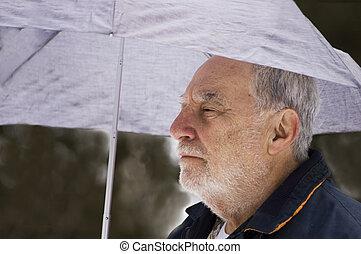 Senior under umbrella