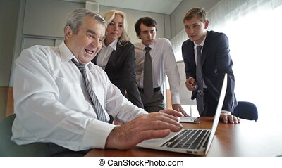 Senior user - Senior businessman using laptop and sharing...