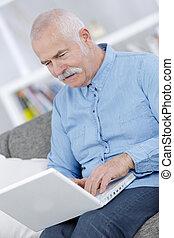 senior using a laptop at home