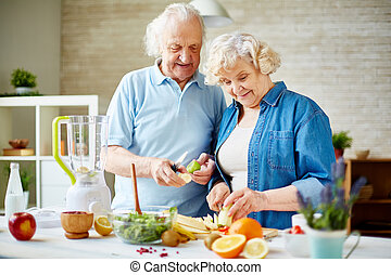 Modern senior couple preparing fresh fruits for making smoothie